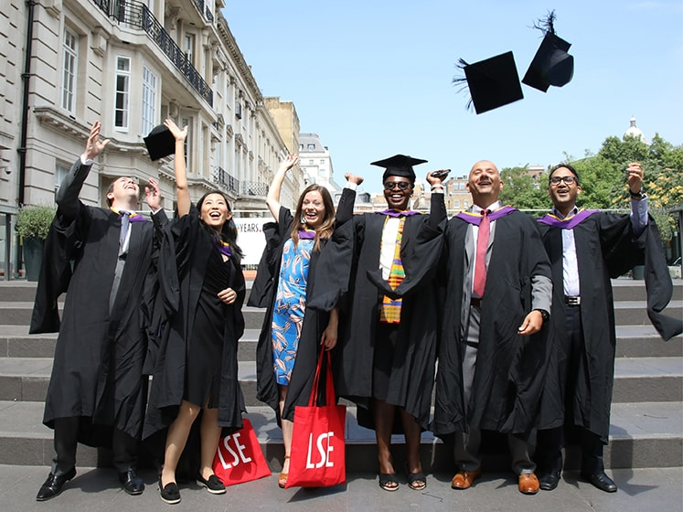 A group of LSE alumni toss mortar boards in celebration