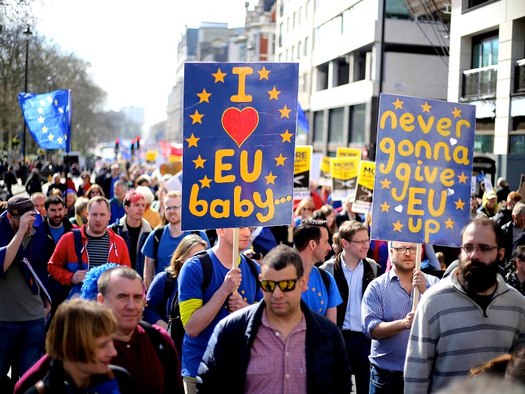 A march with people holding up banners about the European Union.