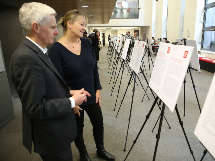 A selection of posters lined up in a row with 2 judges looking | LSE festival research competition