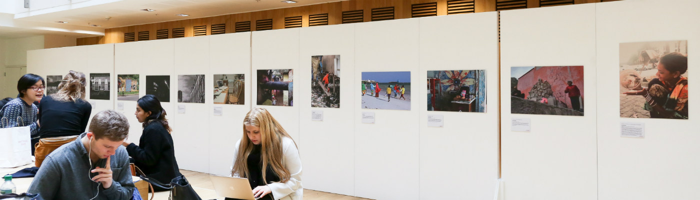A gallery space with photographs displayed and students sitting around.