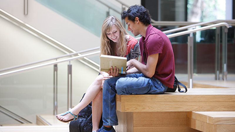 2 students reading a book together in the New Academic Building on the LSE Campus