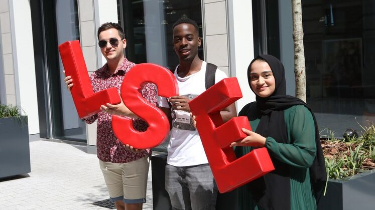 Three LSE students each holding an L-S-E