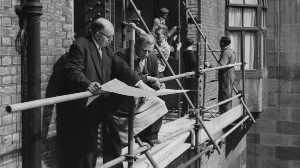 Work on LSE courtyard extension in 1964, two men look at plans while builders in the background work