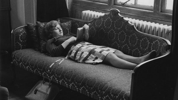 Student reading a book lying on a sofa in the Shaw Library in 1964