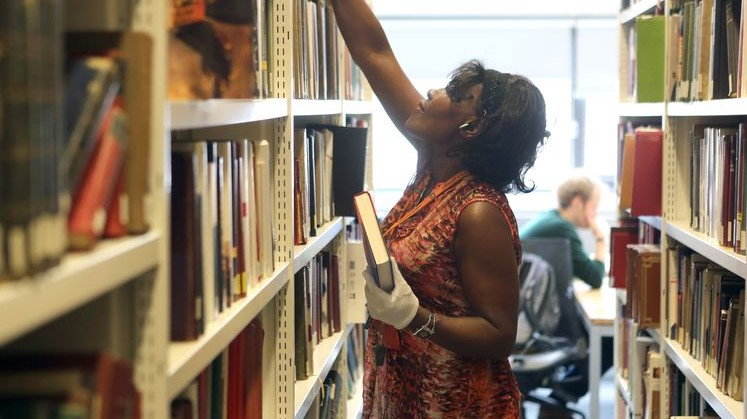 Staff member refilling bookshelves in the Library in 2018