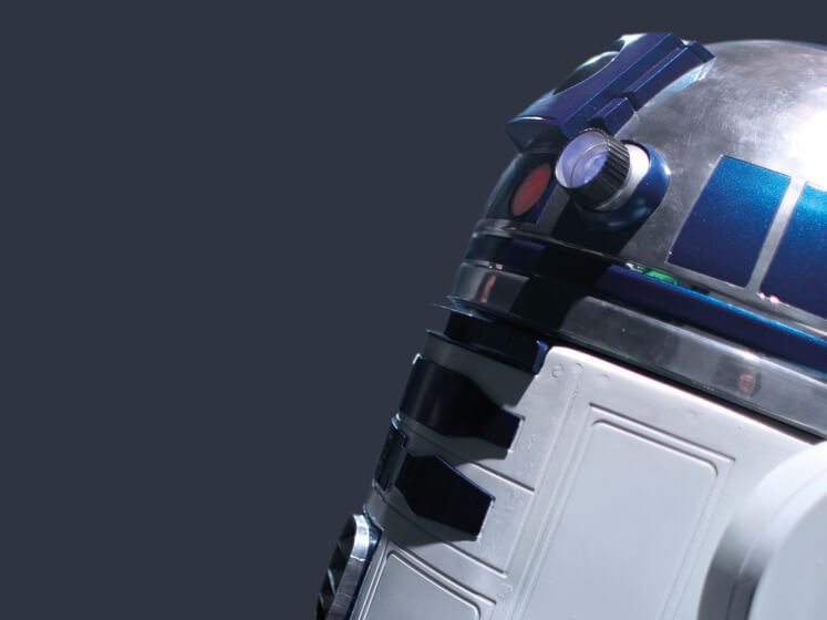 A close-up of a white, blue and silver machine droid from the film Star Wars