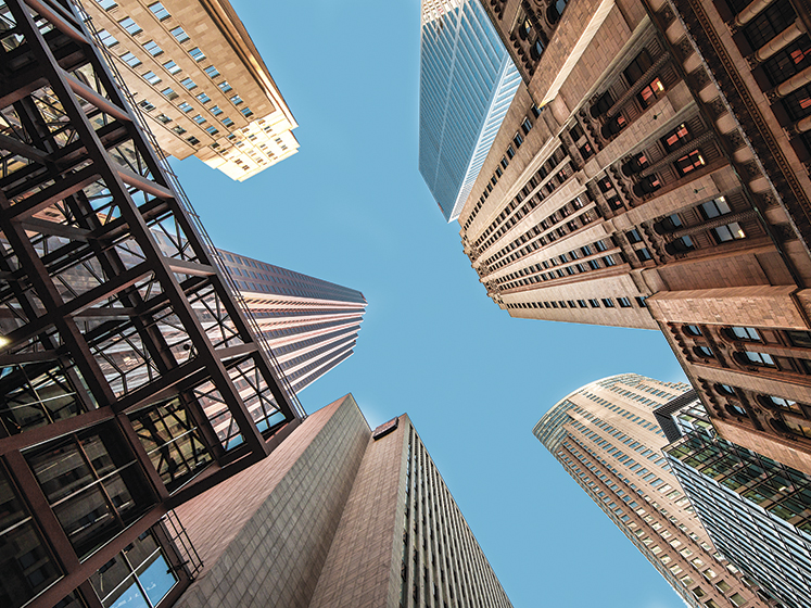 A view of the sky from below some tall buildings