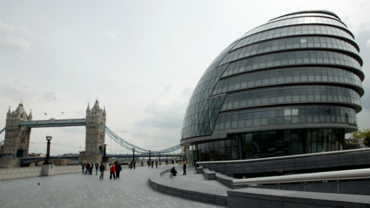 A large modern building beside a bridge | London city hall