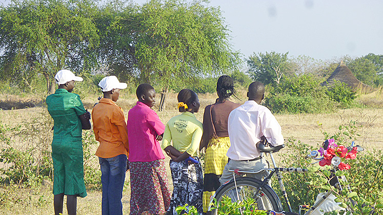 A group of people look into the distance in South Sudan