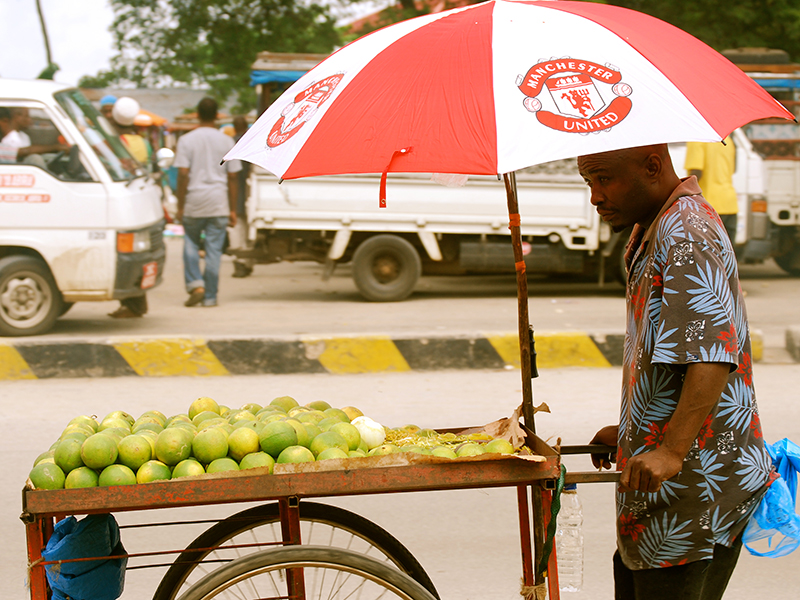 A street hawker pushes a cart of apples with a Manchester United umbrella