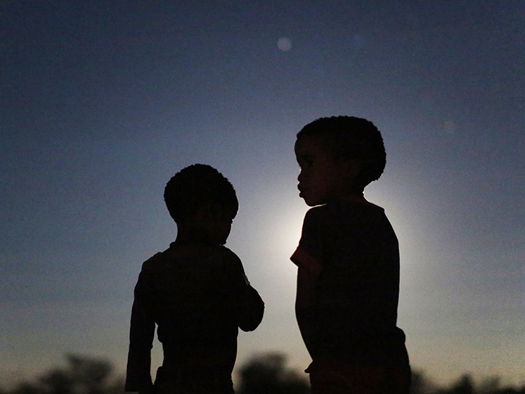 Young boys stand outside on a moonlit night in Namibia