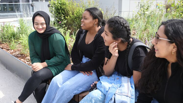 A group of female students laughing and talking while sitting outside on the Centre Building roof terrace