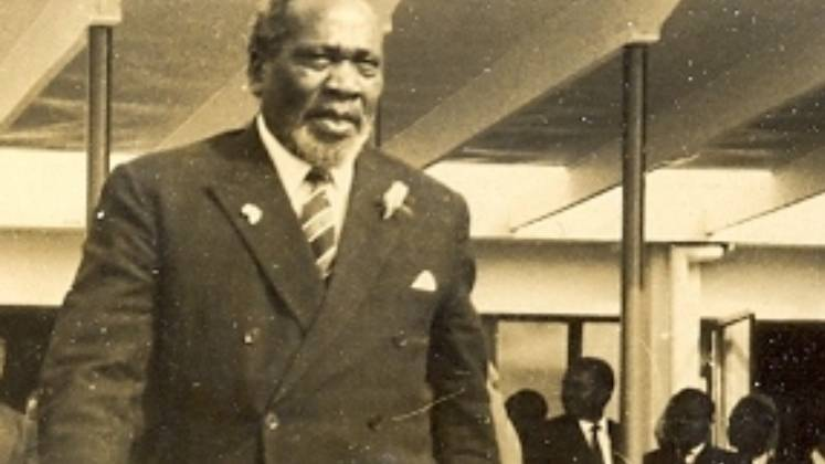 Black and white photo of Jomo Kenyatta walking through a building
