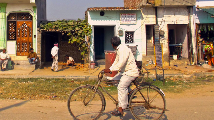 Man ridding bicycle on street in rural India
