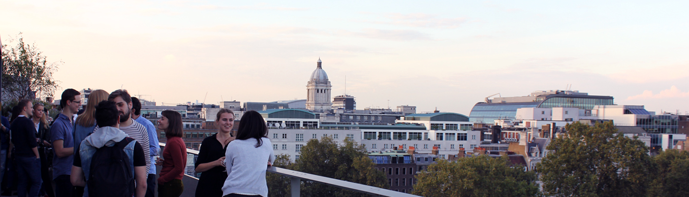 Students socialise on the NAB Terrace during Welcome Week with a view over the London skyline