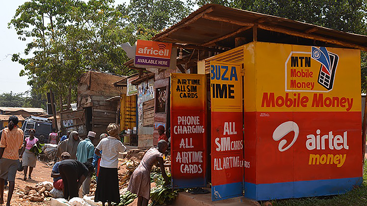 People outside a mobile money kiosk in Uganda