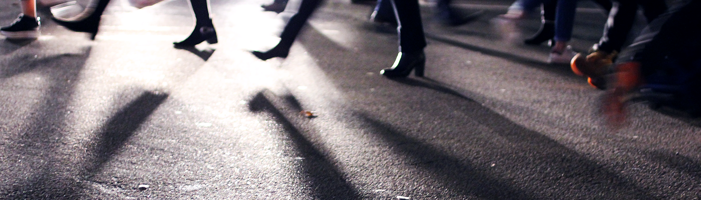 Abstract photo of people's feet walking across a pedestrian crossing casting long shadows in the car headlights.