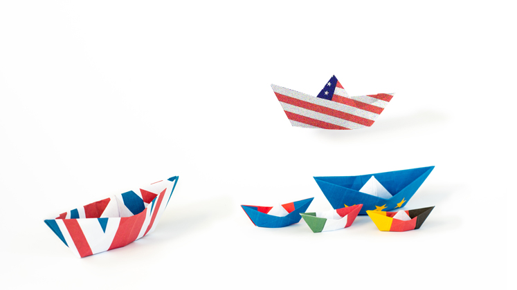 Paper boats with UK, US, France, Italy, Germany and EU flags on them