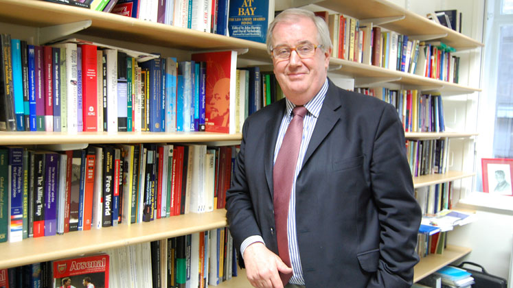 Professor Michael Cox stands in front of bookshelves