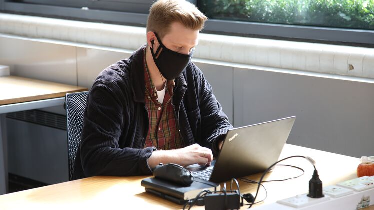 Student wearing a mask sat at a desk using a computer