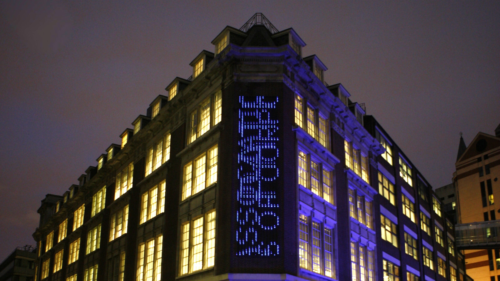 A view of LSE Library from outside at night with a focus on the Bluerain artwork on the corner of the building.