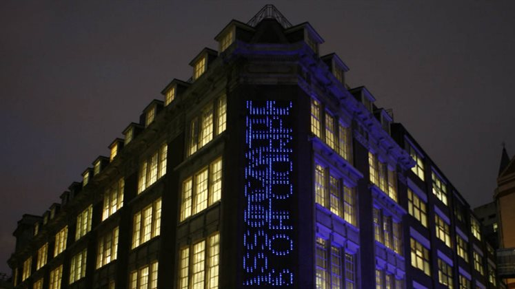 An outside view of LSE Library at night which includes the artwork Bluerain - an installation where searches from the catalogue scroll down from top to bottom on top of each other using blue LED lights.