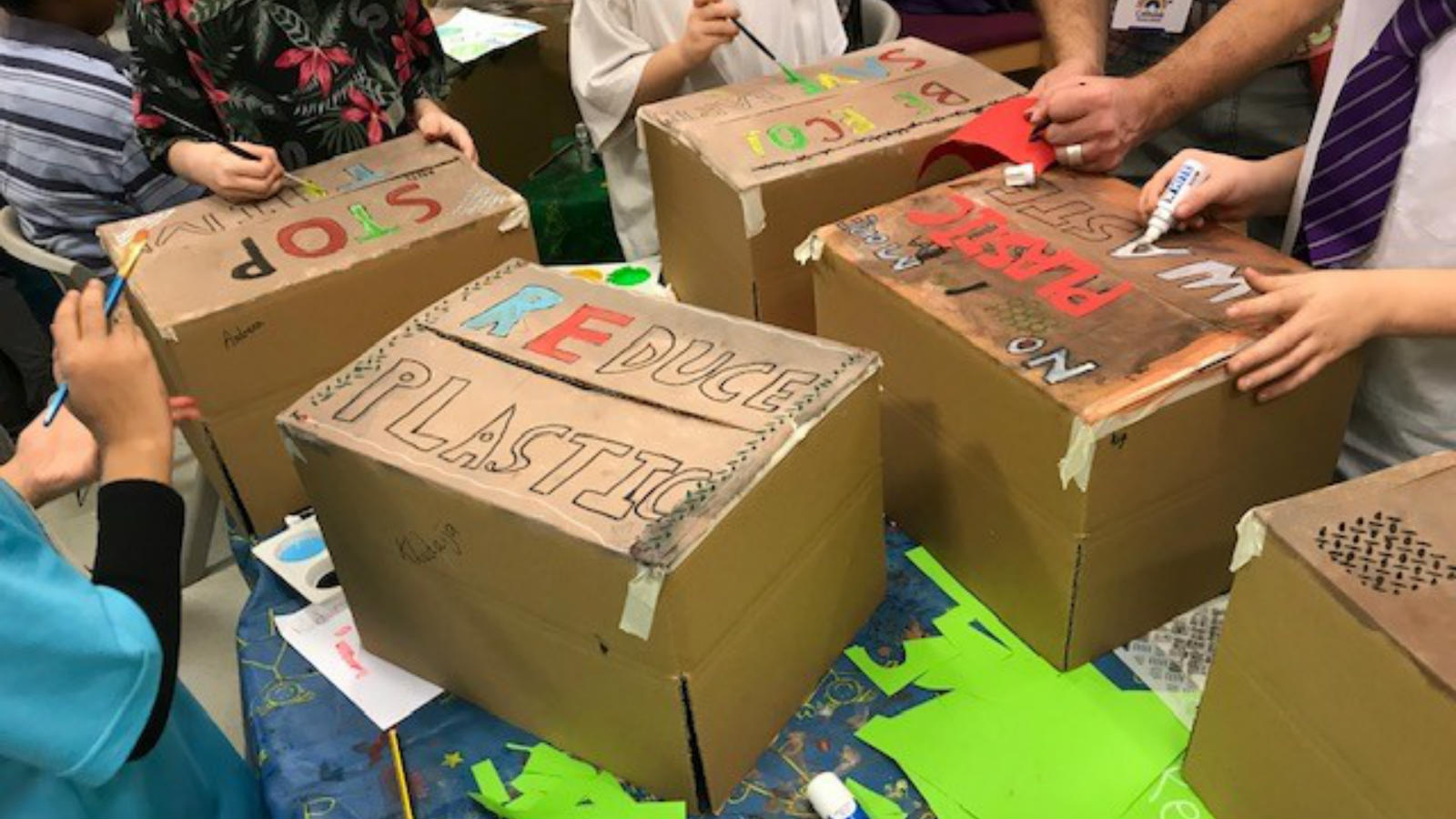 Cardboard boxes that visitors from a school have decorated to contribute to a wall