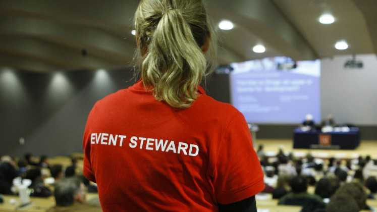 A person is stood wearing an red t-shirt with 'Event Steward' written on the back. They are looking out over the audience of an event.