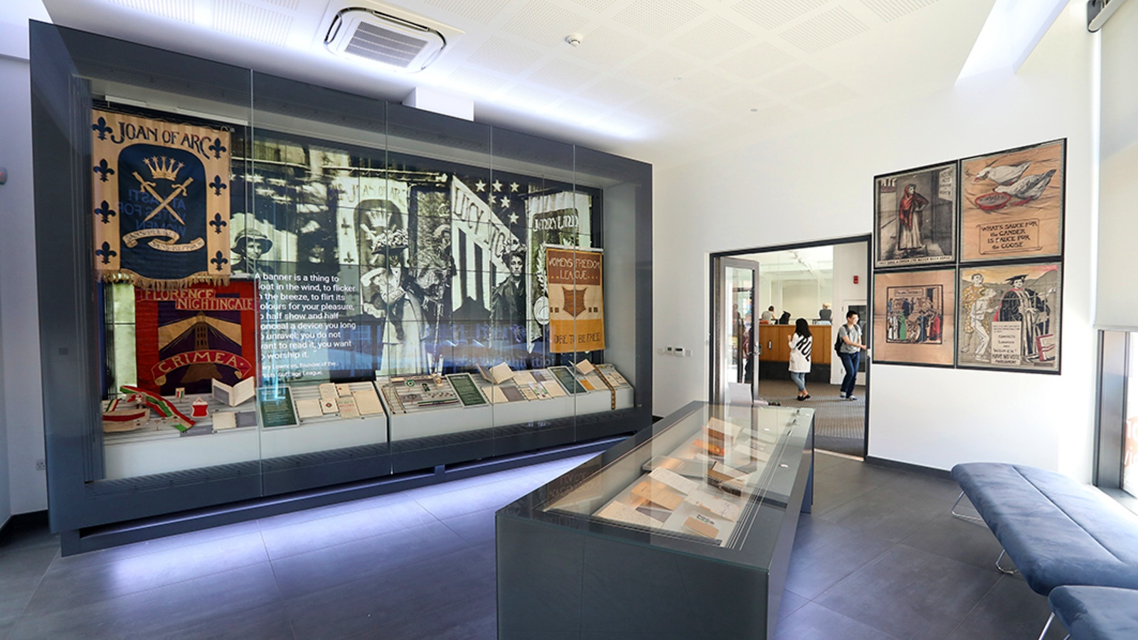 A view of the Exhibition Gallery looking primarily at the large digital screen where images from the exhibition along with various objects are on display. It also includes the main display case with objects in and a view out of the room's door into LSE Library.