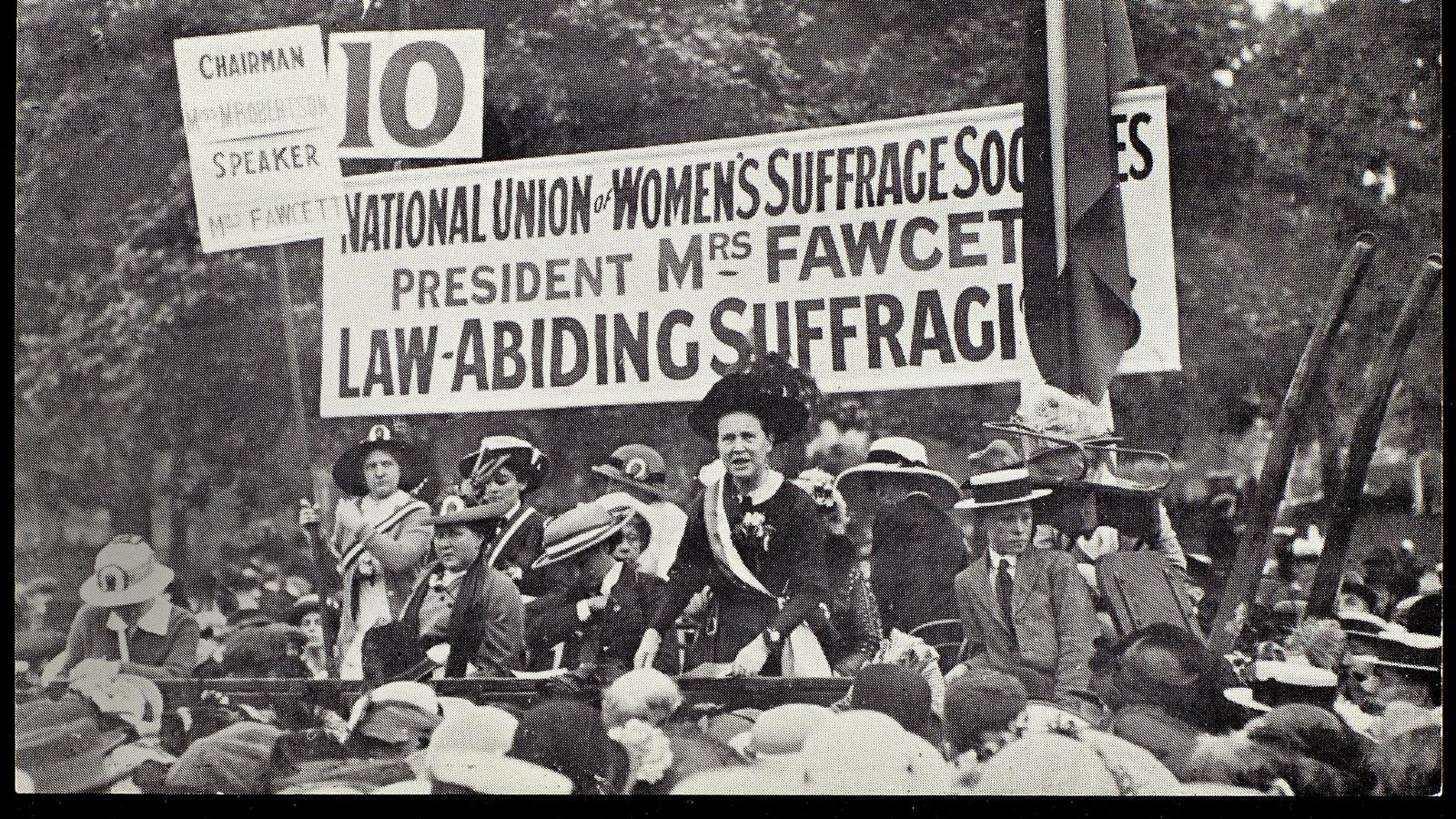 A group of people with banners and placards at a protest looking into the camera. One of them is Millicent Garrett Fawcett who is speaking at this protest as indicated by the banner above her head.