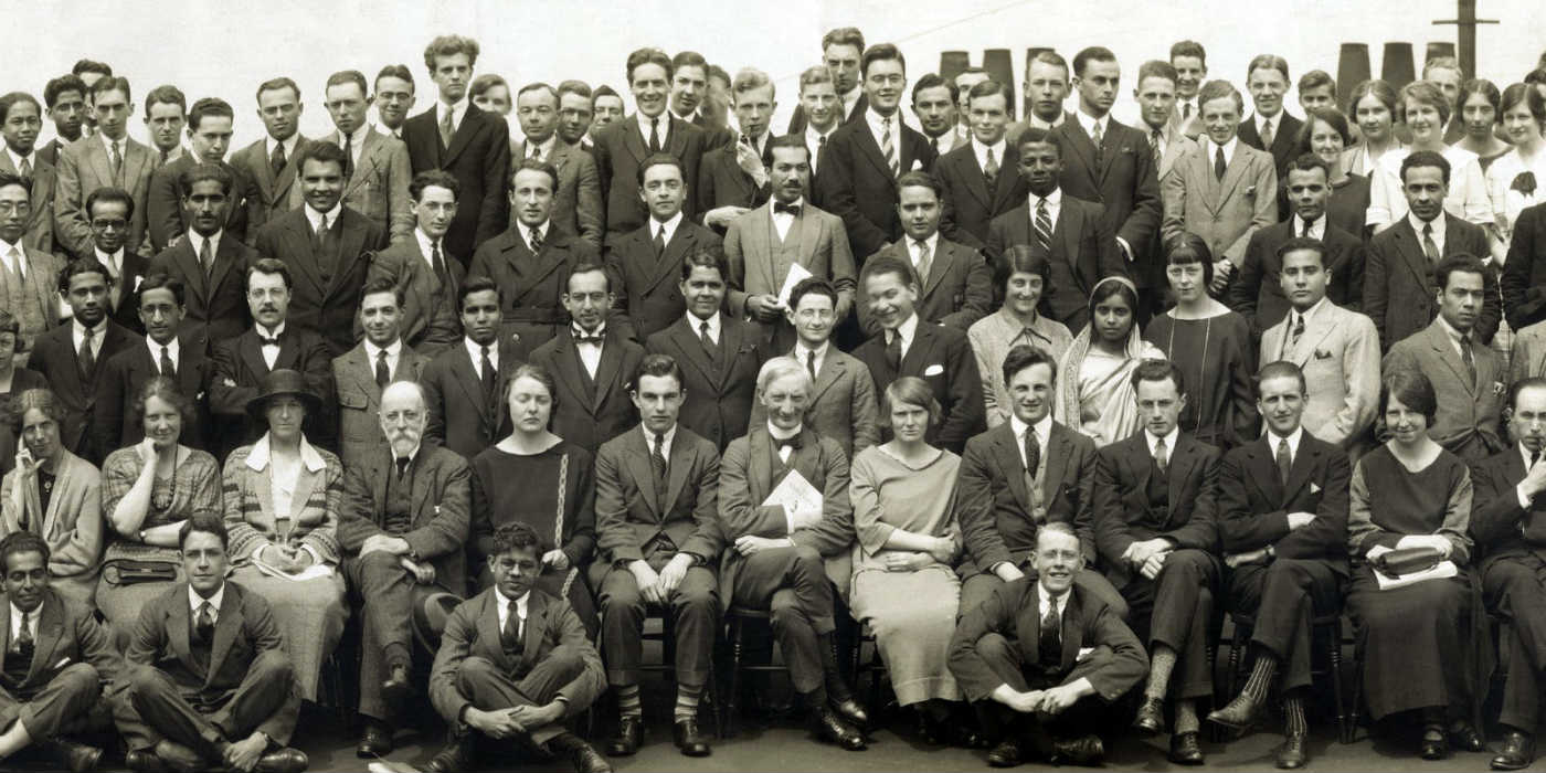 A traditional all school photo where a large group of people are seated and standing looking at the camera for a group photo.