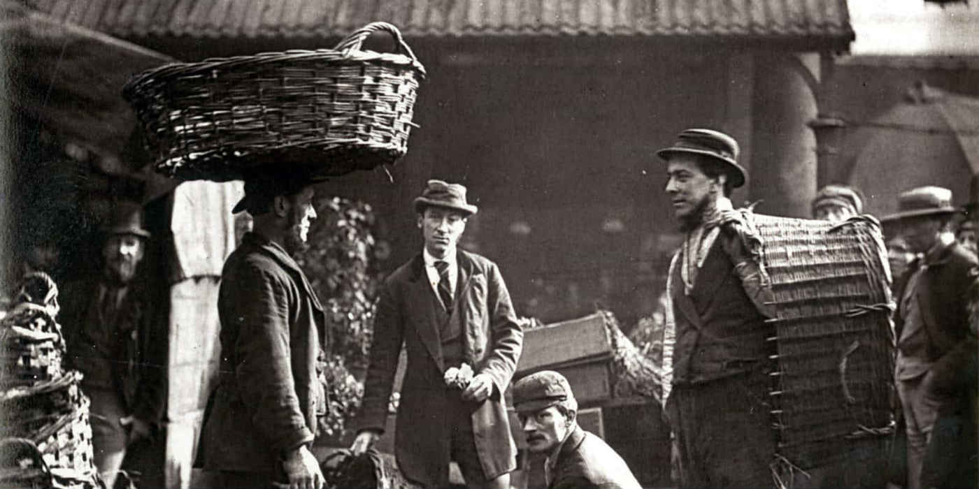 A group of labourers in Victorian London. Some appear to be carrying baskets with one of the labourers carrying a basket on their head.