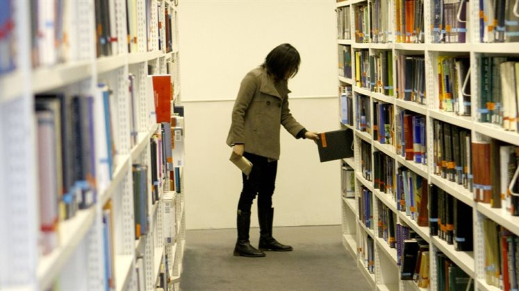 Person in the shelves picking up a book