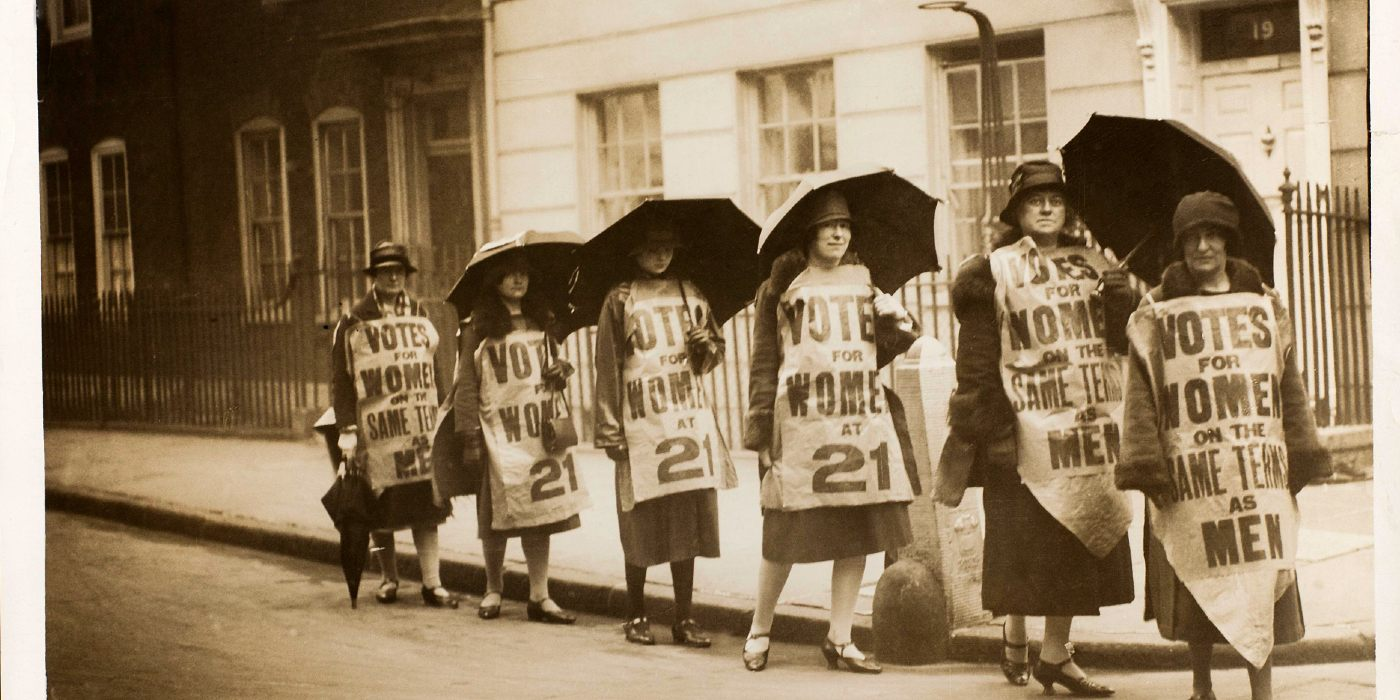 A group of women marching down a street with banners attached to them and carrying umbrellas.