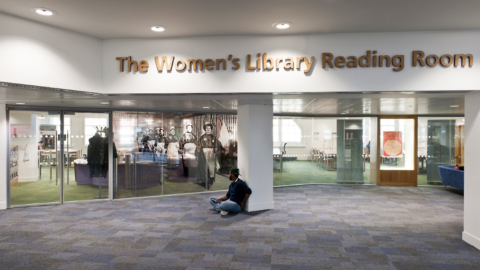 A view on the 4th floor of the Library outside and looking into The Women's Library Reading Room. A student is seated on the floor.