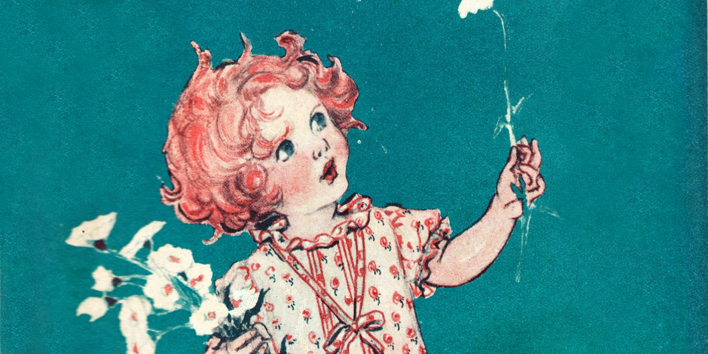 A red-headed girl wearing a dress looking upwards toward a flower she is holding in her hand