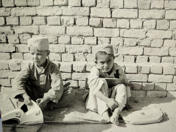 Young boys sat against a wall