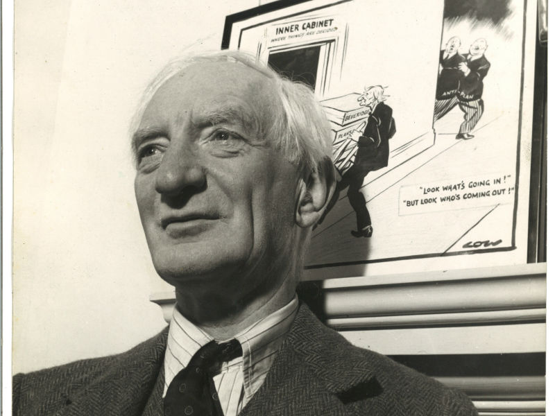 Lord Beveridge standing up against a wall and looking into the distance