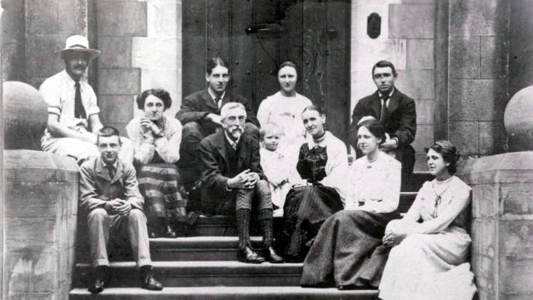 Charles Booth and his family sitting on some steps for a group photo.