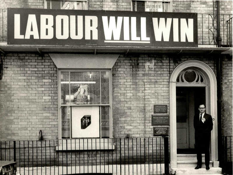 Man stood outside a house with a large 'Labour Will Win' banner on house front.