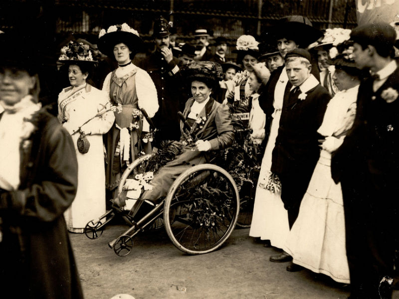 Rosa May Billinghurst sitting in her tricycle surrounded by people
