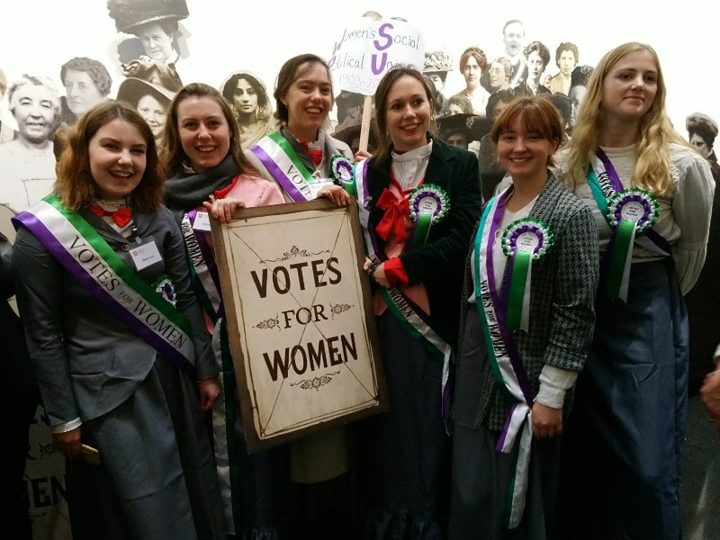 a group of people dressed as suffragettes holding a banner
