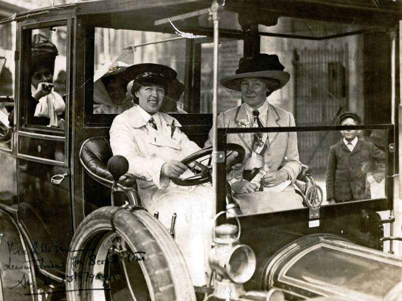 Vera 'Jack' Holme driving a car smiling