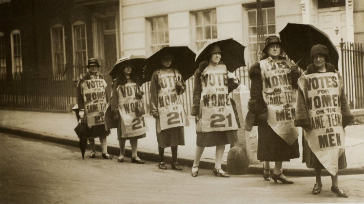 A group of women walking with banners and umbrellas