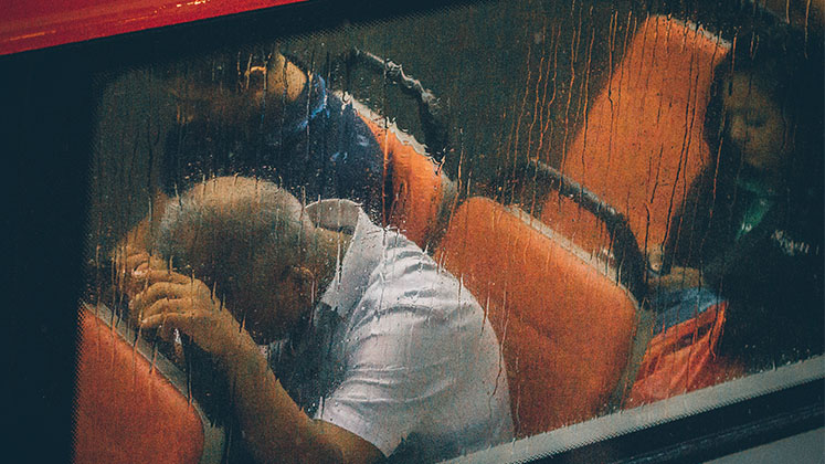 Image of a distressed man sitting on a public bus in the rain