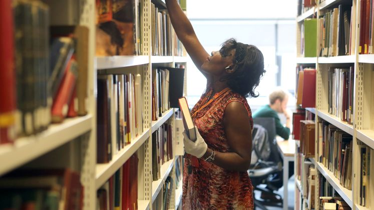 Lady in library reaching for book