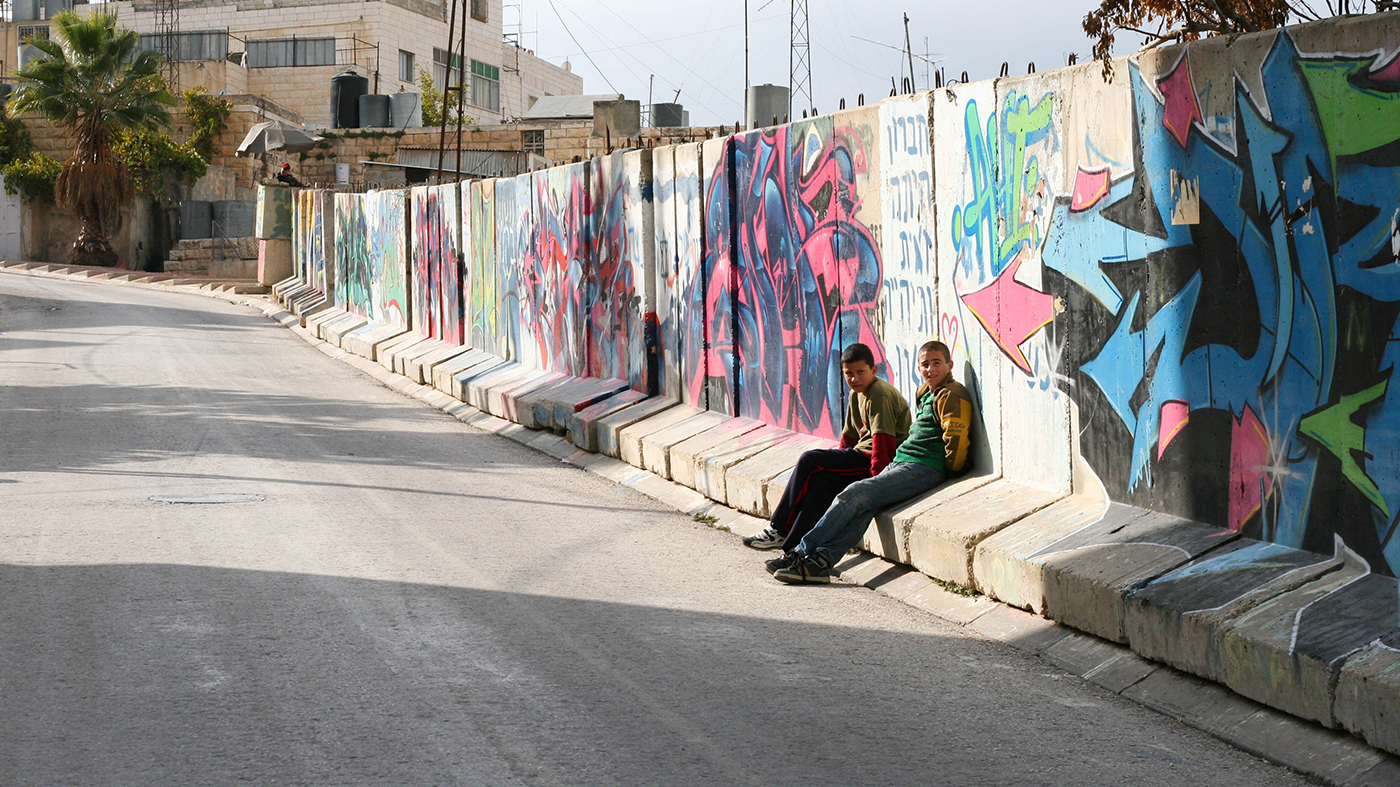 Palestinian boys sitting in front of wall