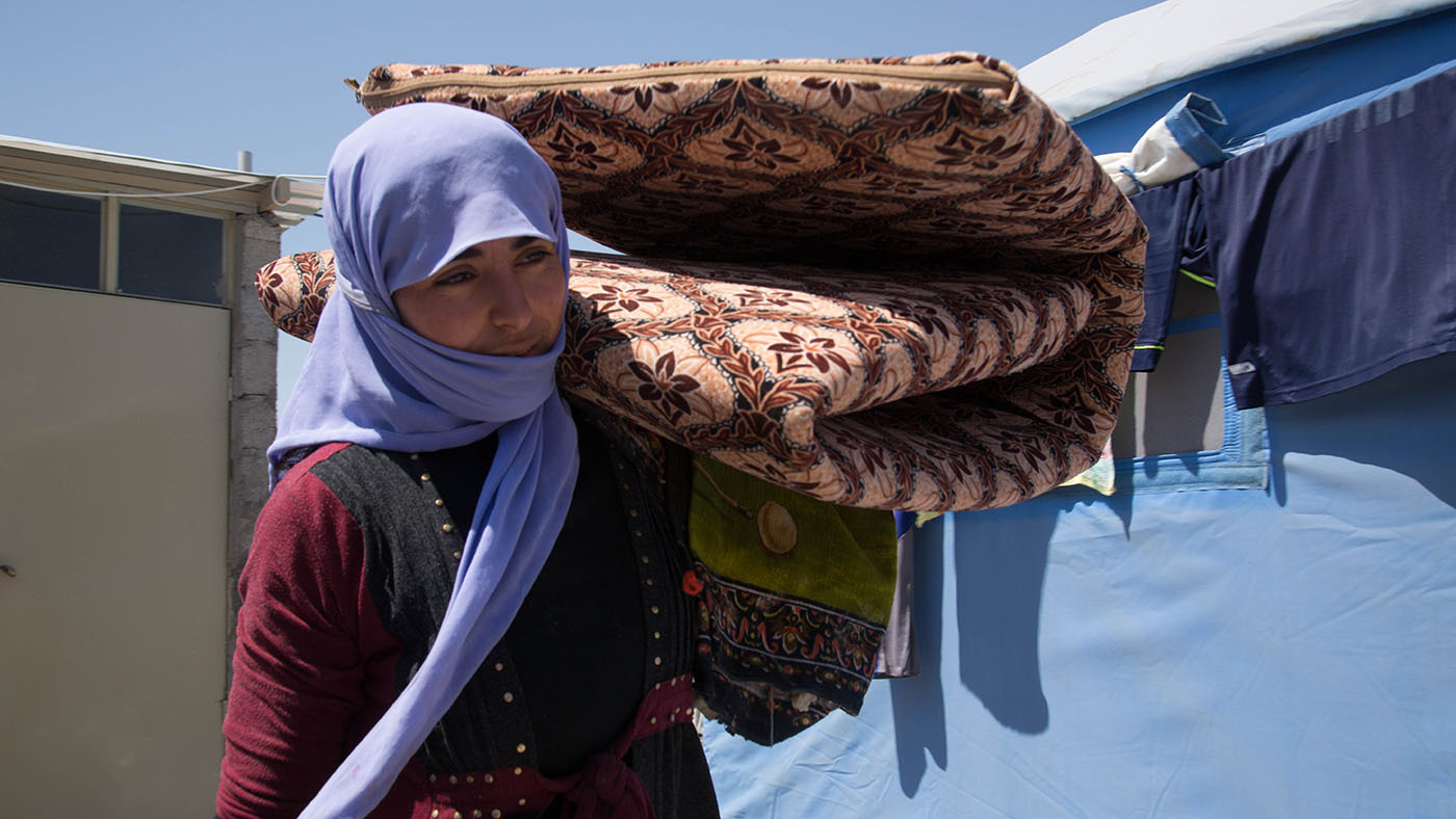 Iraqi internally displaced woman carrying her belongings