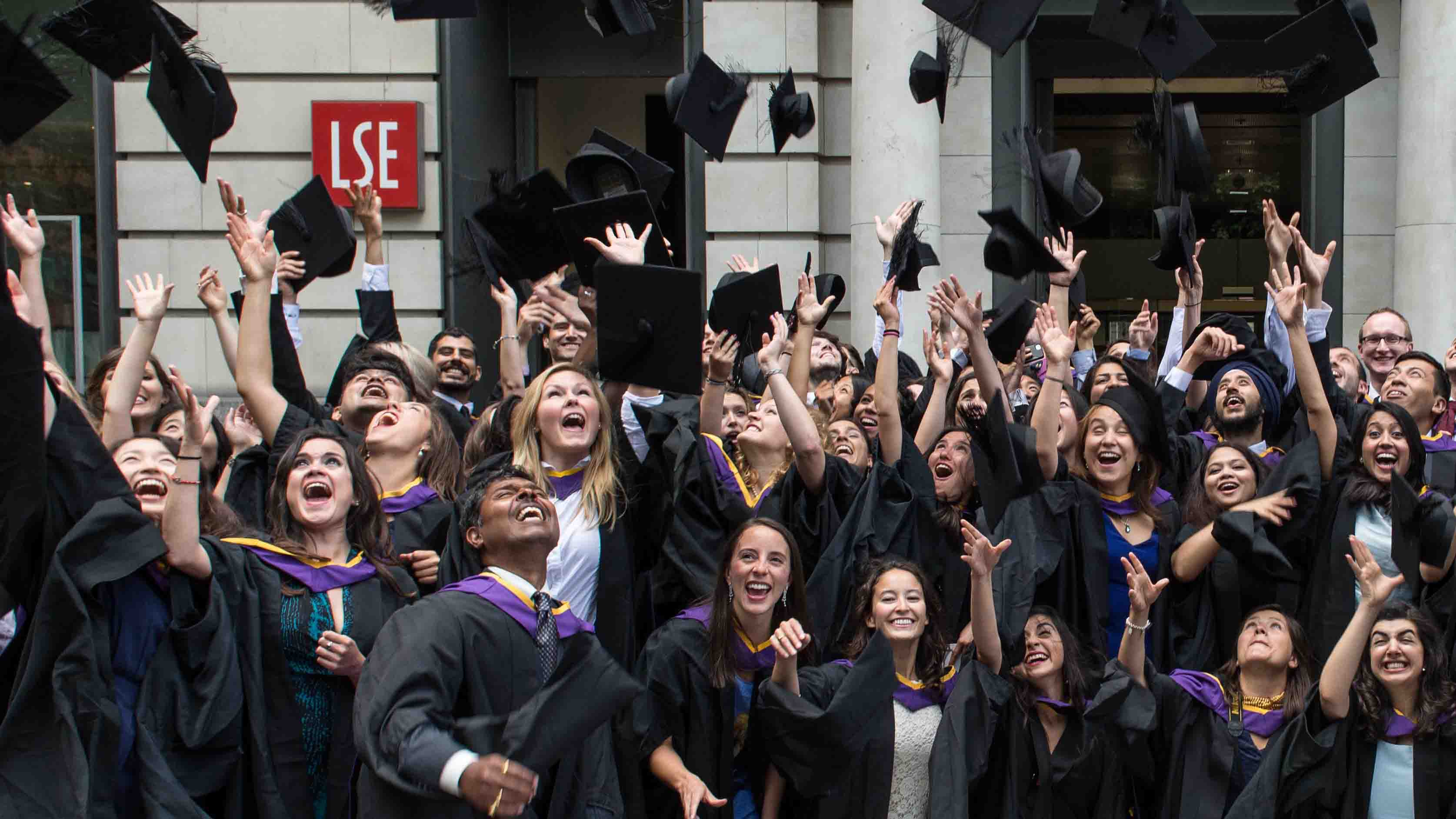 MPA graduates throwing their mortarboards in the air