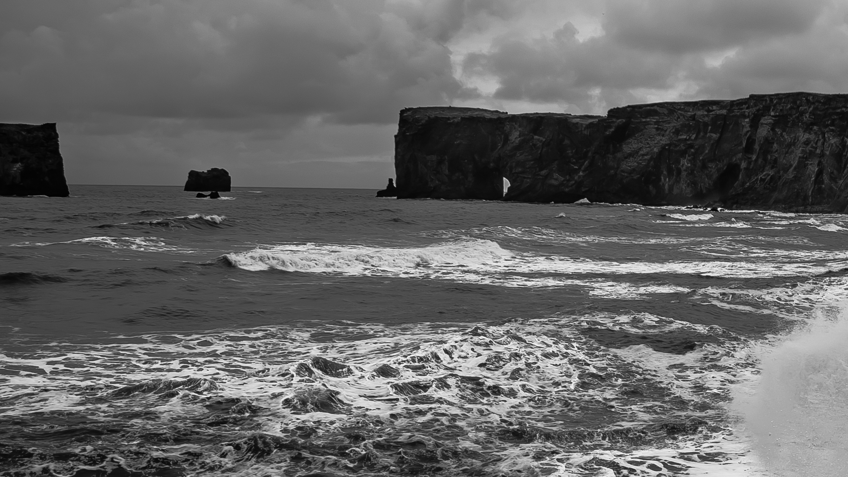 Cliffs surrounding a stormy sea cove